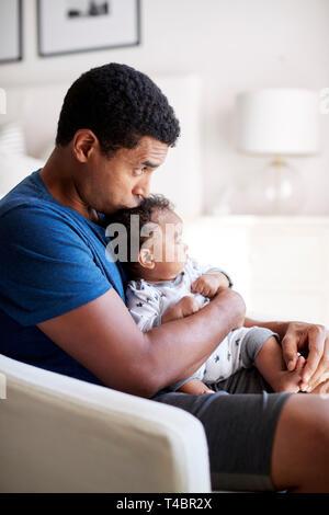 Junge Erwachsene Vater im Sessel halten seine drei Monate alten Baby Sohn und küsste seinen Kopf sitzen, Seitenansicht, in der Nähe - Stockfoto