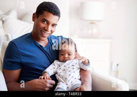 Nahaufnahme von jungen Erwachsenen schwarzen Vaters in einen Sessel seine drei Monate alten Baby Sohn Holding sitzt und lächelt in die Kamera, Vorderansicht - Stockfoto