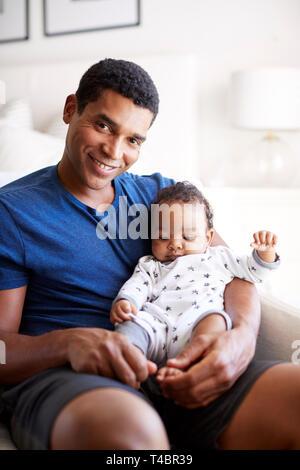 Nahaufnahme von jungen Erwachsenen schwarzen Vaters in einen Sessel seine drei Monate alten Baby Sohn Holding sitzt und lächelt in die Kamera, vertikal - Stockfoto