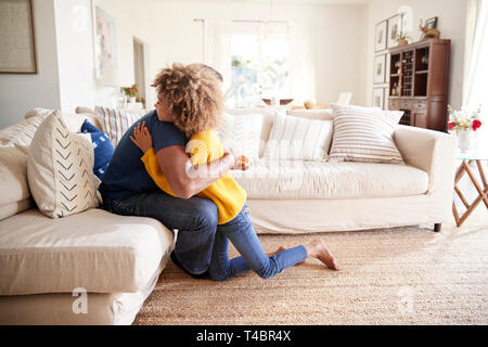 Vor - jugendlich Mädchen ihren Vater im Wohnzimmer nach Ihm eine handgefertigte Geschenk, Seitenansicht umarmen - Stockfoto