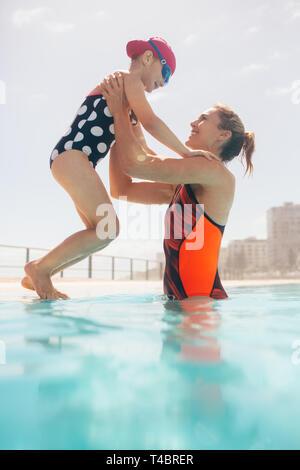 Frau, die ein Mädchen im Pool vom Rand des Pools. Mutter und Tochter am Außenpool. - Stockfoto