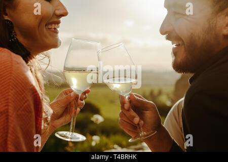 7/8-schuss ein glückliches Paar zusammen lachen Holding Gläser Weisswein. Seitenansicht Nahaufnahme von einem lächelnden Paare miteinander sprechen, Toasten - Stockfoto