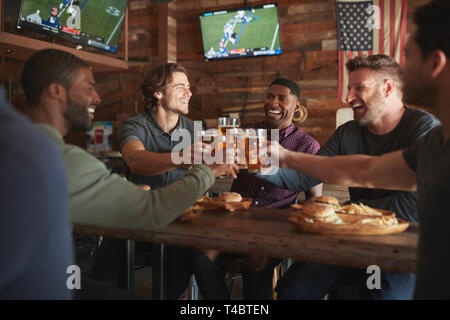 Männliche Freunde Bier trinken und Essen Burger In der Sports Bar - Stockfoto