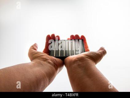 Zwei Hände, die eine Solaranlage auf einem weißen Hintergrund einstellen - Stockfoto