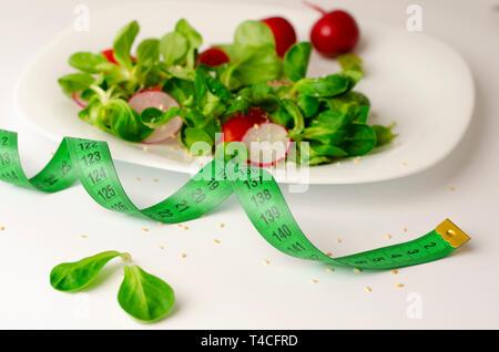 Frisches Gemüse Salat von Rettich, Tomaten und Mais Salat oder Valerianella locusta. Nahaufnahme auf weiße Platte und Maßband. Diät, Gewichtsverlust und sl - Stockfoto