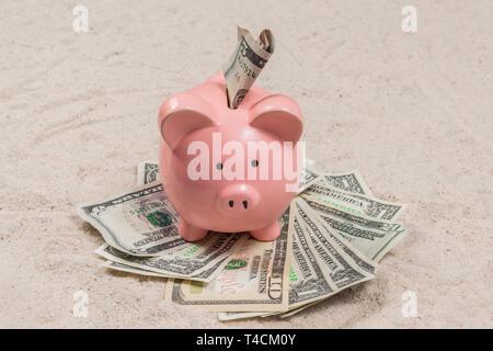 Horizontale geschossen von einem Sparschwein mit Bargeld an einem Sandstrand urlaub Strand. - Stockfoto