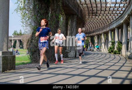 Drei Frauen in t-shirts mit Zahlen laufen Marathon im Park im Frühling. Wroclaw, Polen - 7 April, 2019 - Stockfoto