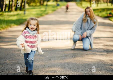 Junge blonde Mutter hinter ihr super energetische toddler Tochter in einem sonnigen Park - Stockfoto
