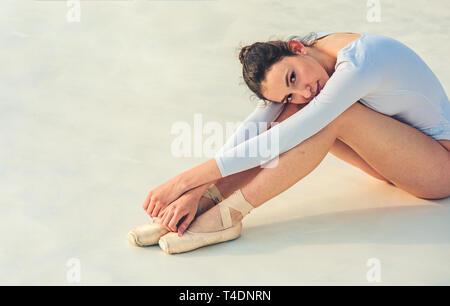 Ich muss mehr üben. Junge Ballerina sitzen auf dem Boden. Cute Ballett Tänzerin. Hübsche Frau im Tanz tragen. Üben die Kunst des klassischen Balletts. Ballet class - Stockfoto