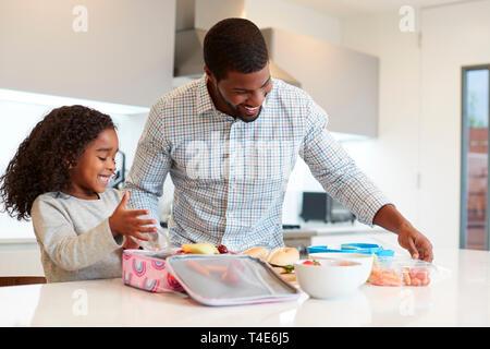 Tochter in der Küche zu Hause helfen Vater gesundes Lunchpaket zu machen - Stockfoto