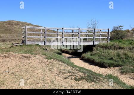 Eine ziemlich große Holzsteg Überquerung eines ausgetrockneten sandigen Boden Creek neben dem Tidal River Ogmore, wo dieser Bereich Gezeiten Hochwasser. - Stockfoto