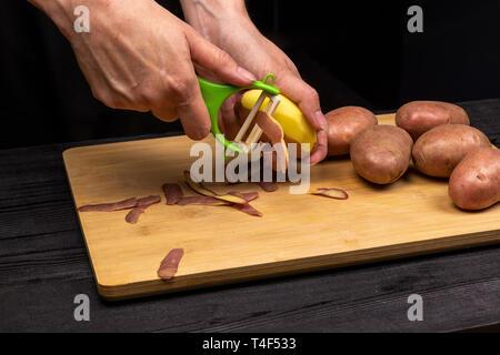 Der Prozess der Reinigung der Kartoffeln mit einem speziellen Messer, Schäler. Der Küchenchef bereitet Kartoffeln zum Braten oder Kochen - Stockfoto
