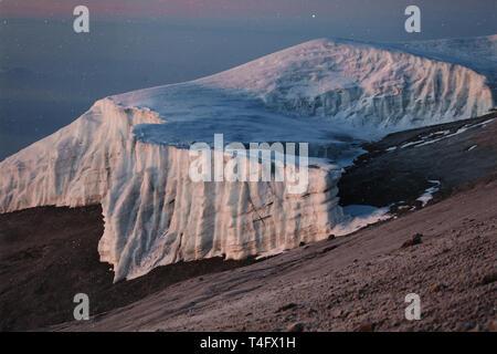 Massive White Ice Teil des Berges bedeckt mit weißen Schnee. Blue Sky im Morgennebel. Dunkle land, nichts Leben, keine Menschen und Bäume. - Stockfoto