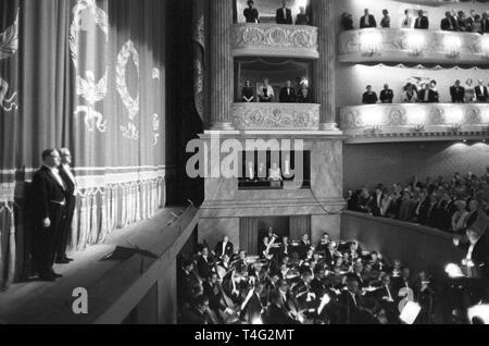 Das Publikum zahlt Respekt zu den verstorbenen Präsidenten während Joseph Keilberth die amerikanische Nationalhymne vor Eröffnung des neuen Nationaltheaters in München am 23. November führt. US-Präsident John F. Kennedy wurde am 22. November 1963 in Dallas ermordet (Tx).   Verwendung weltweit - Stockfoto