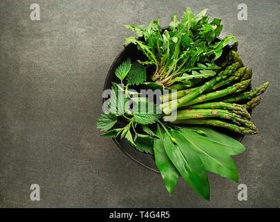 Frühling gesundes Essen. Löwenzahn, Bärlauch, Brennnessel und Spargel in der Schüssel - Stockfoto