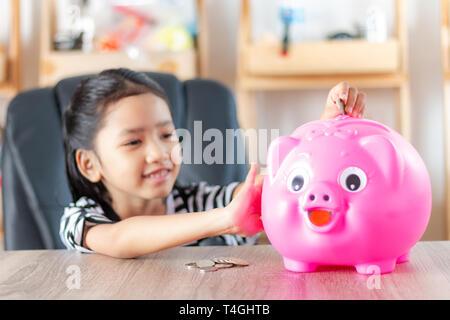 Asiatische Mädchen in die Münze in die piggy Bank geringe Tiefenschärfe wählen Sie Fokus am Schwein - Stockfoto