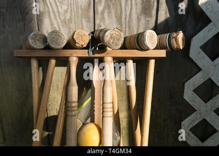 Alte gut genutzt Croquet Mallets in einem Rack, lehnte sich gegen eine Holzwand, mittellange Aufnahme - Stockfoto