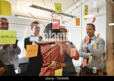 Zwei lächelnde junge Unternehmerinnen umarmen beim Brainstorming mit Haftnotizen auf eine Glaswand mit coworrkers in einem modernen Büro - Stockfoto