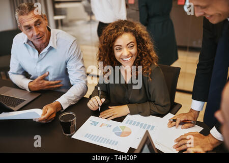 Lächelnden jungen Geschäftsfrau über Graphen mit Kollegen während einer Sitzung in einem Büro Sitzungssaal - Stockfoto