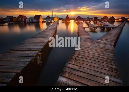 Sonnenuntergang über dem See Bokod mit hölzernen Pier und schwimmende Häuser, Ungarn - Stockfoto