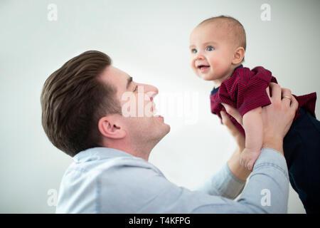Vater Anheben Lächelnden Sohn in die Luft zu Hause, wie Sie spielen Gane zusammen - Stockfoto