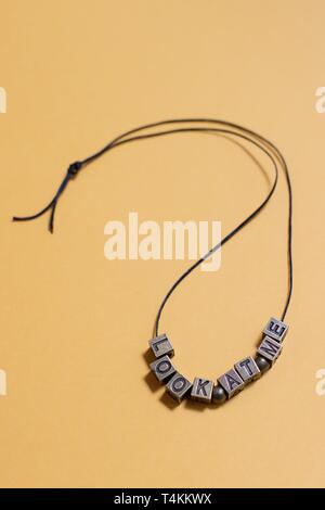 """Die Worte """"Schau mich an"""" von Buchstaben Perlen auf einer Kette geschrieben. - Stockfoto"""