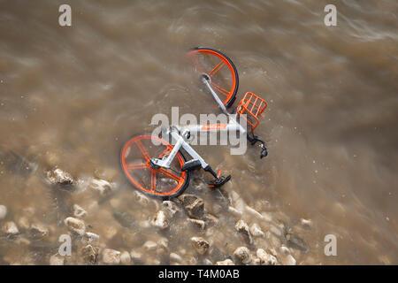 River Water laps über eine weggeworfene Mobike Fahrrad am Ufer in den Fluss Themse durch Vandalen in der Nähe von Westminster Bridge geworfen - Stockfoto