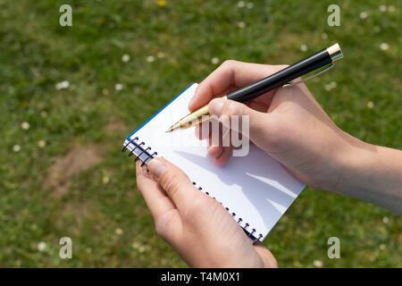 Boy's Hand mit einem gelb-schwarzen Stift über einem offenen Notepad auf dem Hintergrund des grünen Grases und weißen Blumen im Park. Sauberes weißes Blatt. Zu w - Stockfoto