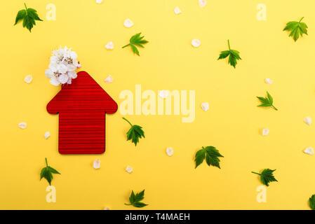 Red toy House, weißen Blüten auf gelbem Hintergrund mit grünen Blättern. Immobilien Geschäftskonzept, Platz für Text, bezahlbaren Wohnraum für Familien Stockfoto