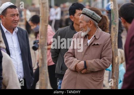 Bärtige uigurischen Mann mit einem doppa (traditionelle Hut) lehnte sich an einem Pol, in Kashgar Tiermarkt (Provinz Xinjiang, China) - Stockfoto
