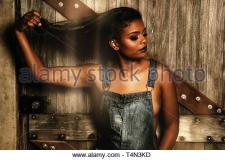 Frau tragen graue Overalls lehnte sich auf braune hölzerne Wand - Stockfoto