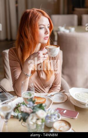 Schöne rothaarige Frau essen Frühstück im Cafe. Porträt der jungen hübschen Frau trinkt Kaffee und getoastetes Sandwich in der modernen Coffee Shop. - Stockfoto
