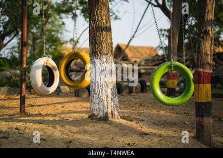 Farbe alte Autoreifen hängen am Baum am Spielplatz - Stockfoto