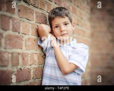 Junge, 7 Jahre, lehnte sich gegen eine Wand, Porträt, Deutschland - Stockfoto