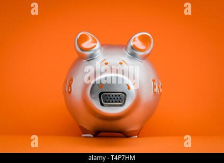 Metallic farbigen Sparschwein auf orangefarbenem Hintergrund mit elektrische Schnittstelle Steckverbinder am Schwein Nase. (Manipulierte) - Stockfoto