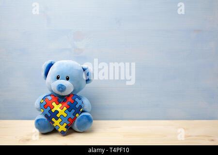 Welt Autismus Bewußtsein Tag, Konzept mit Teddybär holding Puzzle oder Stichsäge Muster auf Herz - Stockfoto