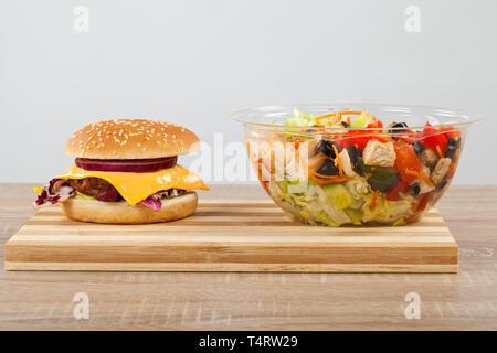 Leckere Cheeseburger und Salat auf einem hölzernen Schneidebrett - Stockfoto