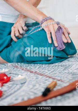 Frau mit lila mala Perlen auf Ihre Hände mit Henna mehendi - Stockfoto