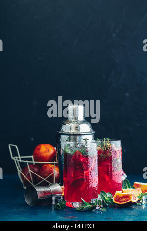 Cocktail highball Bloody orange Margarita im Glas. Im Sommer erfrischende Getränke. Cocktail Blutorange Margarita, in Gläsern auf einem dunkelblauen konkrete Tabl