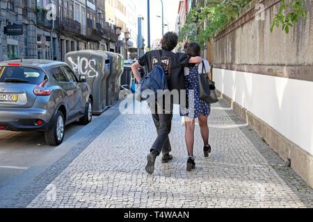 Junges Paar Rückseite Rückseite gehen gemeinsam entlang der Rua De Cedofeita gehsteig Bürgersteig nach der Arbeit im Frühjahr Porto Portugal Europa EU-KATHY DEWITT - Stockfoto