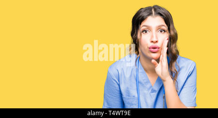 Junger Erwachsener Arzt Frau mit medizinischen einheitliche Hand auf Mund, geheime Gerücht, Flüstern bösartige talk Gespräch - Stockfoto