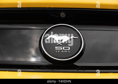Das Logo von einem gelben 2015 50-jähriges Jubiläum Ford Mustang Symbol auf der Rückseite des Autos mit Wassertropfen. - Stockfoto