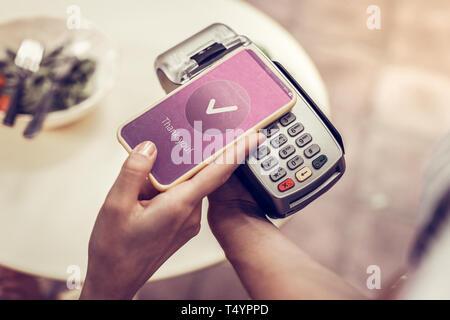 Angenehme junge Frau mit ihrem Smartphone für die Zahlung - Stockfoto