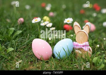 Ostern Jagd - Blau und Rosa Eier und Holz- Bunny in einem Gras - Stockfoto