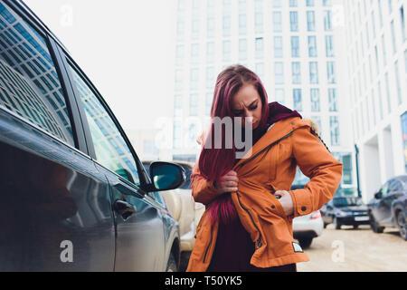 Hübsche junge Frau stehen und die Schlüssel des Autos in ihrer Tasche im Freien. - Stockfoto