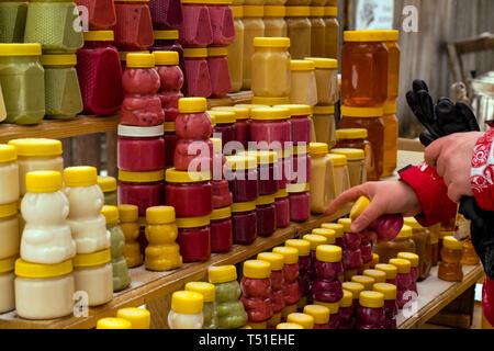 Mädchen mit Handschuhen wählt, Honig und Spezialitäten auf der Theke im Winter - Stockfoto
