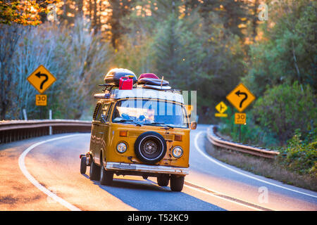 Alte schäbige beliebt wie ein mini Motor home für Reisen gelbe Mini Van mit Reserverad auf der Vorderseite geladen mit Camping Ausrüstung fährt auf einer Biegung eines - Stockfoto