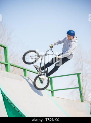 Ein Mann führt Tricks auf dem Fahrrad auf der half pipes - Stockfoto