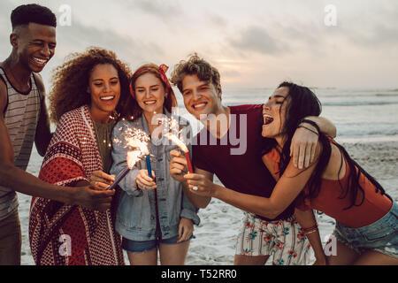 Gerne Freunde feiern am Strand mit Wunderkerzen. Multi-ethnischen Gruppe von Freunden sind, die zusammen am Strand Feiern mit Feuerwerk. - Stockfoto