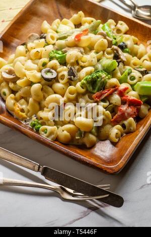Italienisch-amerikanische Küche pipette Pasta Primavera mit cremigen Alfredo Sauce auf Holzplatte - Stockfoto